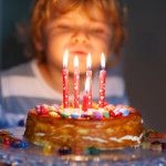 Kid Boy Celebrating His Birthday And Blowing Candles On Cake